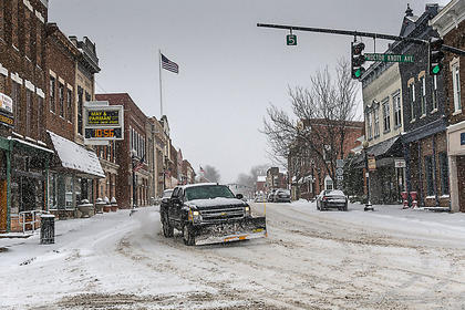A snow plow passes by on Main Street in Lebanon.