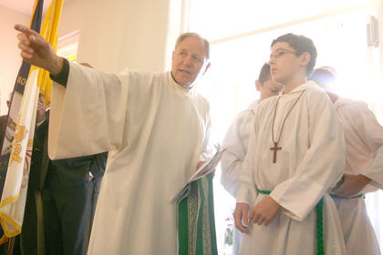 Rev. Jim Graf, the pastor of St. Charles, shares a few last-minute instructions with the servers before the Mass begins.