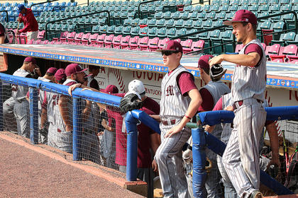The team gets settled in the dugout after arriving at the field.