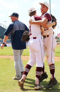 Luke Thomas and Kelly Mattingly celebrate after Thomas' catch of a pop-fly over the first-base dugout to end the game.