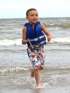 Madax Webb chases after his sister with a handful of sand at Myrtle Beach.