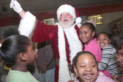 Santa Claus was greeted by a throng of happy children upon his arrival.