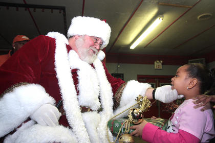 "With help from his ""elves"", Santa distributed gifts to all the girls and boys."