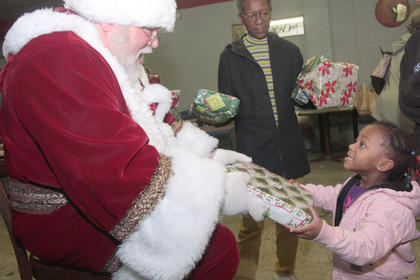 Tahlia Hall, 3, tells Santa thank you after receiving her gift. Lois Epps helped Santa pass out the gifts.