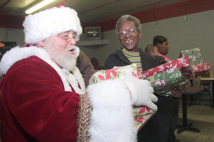 Lois Epps hands a gift to Santa.