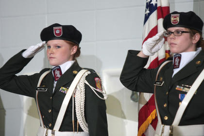 Color guard members Amber Mattingly (left) and Holly Garrett salute during the national anthem.