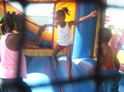 Shamiya Calhoun, 3 (center), jumps on a bouncy.