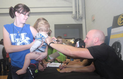 Aaron Branch signs the back of 1-year-old Brayden Wohner's shirt after Building 429's performance Friday night. Whitney Newberry of Gravel Switch is holding Brayden.