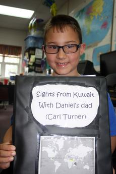 "<div class=""source"">Stevie Lowery</div><div class=""image-desc"">Daniel Turner, 8, proudly shows off his special scrapbook containing all of the emails and photos his father, Carl, has emailed him during his work in Kuwait.</div><div class=""buy-pic""><a href=""/photo_select/26888"">Buy this photo</a></div>"