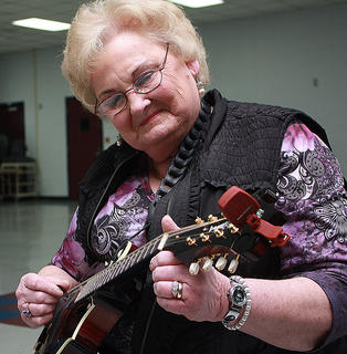 Wanda Runner of Bloomfield, Tenn., carefully tunes her mandolin before participating in a musical workshop at the 2013 Kentucky Bluegrass Music Kickoff.