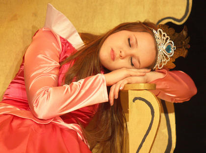 Adria Whitfill, as Princess Aurora, was under a sleeping spell cast upon her by the evil Maleficent during a production of Disney's Sleeping Beauty Kids in May.