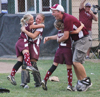 Assistant Coach Joe Pat Cecil hugs Addi Murphy as Haley Mattingly and Cassidy Logsdon embrace in celebration after the 9- and 10-year-old Marion County All-Star softball team won the Little League state championship in July.