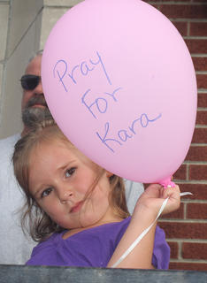 Kara Tingle Rigdon's 3-year-old daughter, Nora, holds one of the balloons that was released during a prayer service at Gravel Switch Baptist Church. Her mother has been missing for more than two years. She was last seen on July 17, 2010.