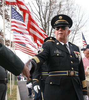 Lynn Farmer of the Marion County Veterans Honor Guard shakes hands with a member of the crowd as the honor guard walks in to start the Veterans Day ceremony.