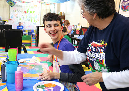Evan Martin smiles proudly after finishing his painting with the help of volunteer Margaret Brockman.