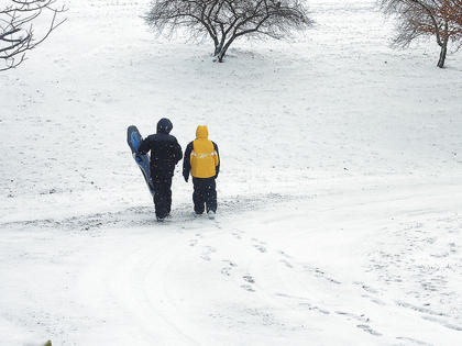 Clay Callahan and Ethan Hunt walk down a snow-covered hill while sledding on Sunday, Dec. 26.