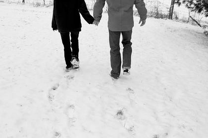 Mignon and Ryan Carter hold hands while walking through the snow