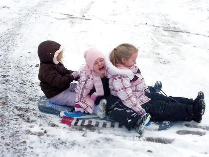 Peyton Leake, Gracie Hunt and Morgan Hunt laugh as they enjoy an afternoon of sledding.