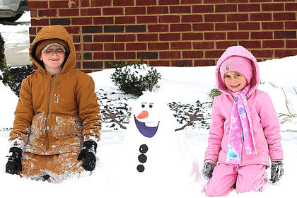 Thomas and Hailee Carrico proudly pose for a photo with their snowman that looks like Olaf from the movie Frozen. Photo submitted by Amanda Carrico.