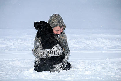 Baylor Murphy and his dog Bo play in the snow.