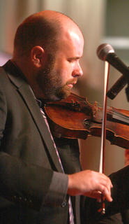 Justen Haynes plays the fiddle with Russell Moore and IIIrd Tyme Out during the final act of Saturday evening's show.
