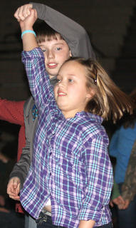 Ally Mattingly and Michael Ryan Masterson perform a traditional Appalachian folk dance Friday evening with students from Calvary Elementary School.