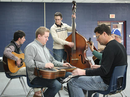 Two small groups of string players began to jam together in bluegrass harmony.
