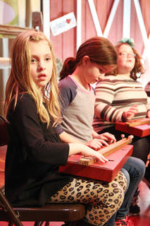 Olivia Spalding plays a dulcimer with her fellow Calvary Elementary School classmates Friday evening.