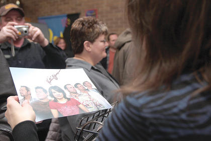 Kristen Scott Benson, the banjo player for the Grascals, returns a signed photo to a fan after Saturday night's performance.