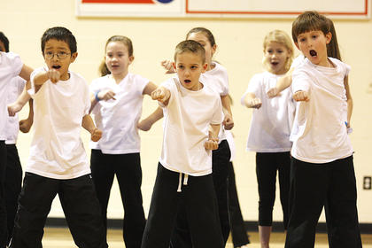 Second and third grade students perform a karate routine.