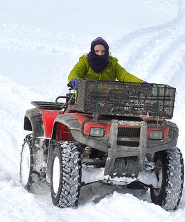 Rose Caldwell drives a four-wheeler in the snow.