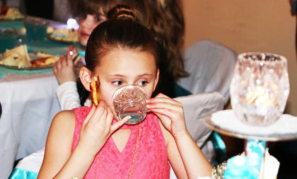 A guest sips her special blue tea, pinky up, at the Frozen Tea Party at Centre Square on Saturday, Feb. 17.