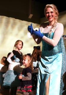 Queen Anna helping a few guests during a game of making toilet paper snowmen at the Frozen Tea Party at Centre Square on Saturday, Feb. 17.