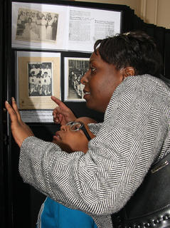 Vanessa Biggers and her daughter, Imani, examine some of the panel displays at the exhibit.