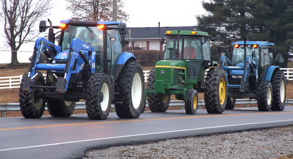 The tractors follow one another down US 68 on the way to school.