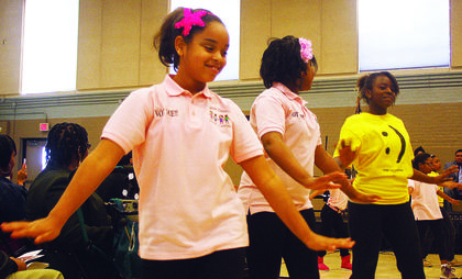 Mercede Douglas performs a dance routine with members of the Marion County Youth Center.