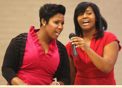 Alicia Johnson, left, and Crystal Neal, both Lebanon natives and part of the McElroy family, sing together during Sunday's celebration.