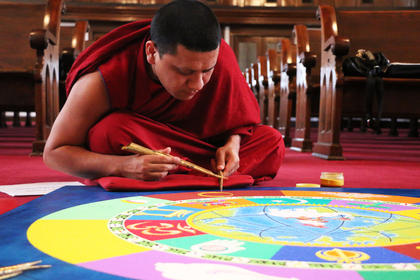 It takes careful precision to lay each grain of sand on the mural, as Tenzin Gyatso demonstrates.