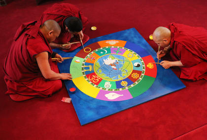 Kalsang Jinpa, Tenzin Gyatso, Yeshi Rabgya work together to finish up the mandala.
