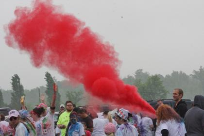 A staff member of the Color in Motion sends out a spray of color before the 5K started on Saturday morning.