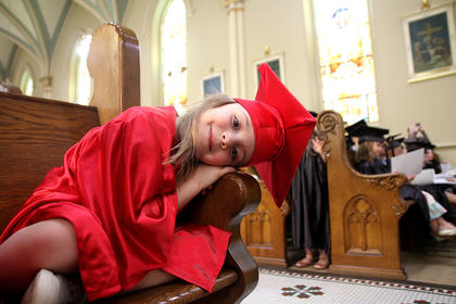 Lilly Thomas, 3, lays her head down on the arm rest of a church pew in St. Augustine Catholic Church during the preschool graduation ceremony.