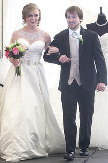 Rachel Rodgers plays the part of a blushing bride as she is escorted by Jacob Giles on the runway.