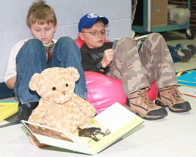 Jakoby Holloway, left, and Cody Raley found a cozy spot to read, along with a reading companion.