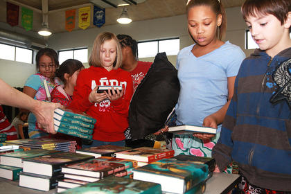 Avery Smith (red sweatshirt), Jazmine Johnson and Elijah Livers pick up free books donated to LES by the First Book organization.