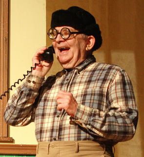 Petey Fisk (Lynn Farris) of the Greater Tuna Humane Society takes a call from Bertha Bumiller.