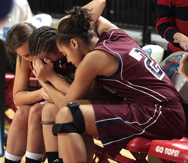 Lady Knights comfort one another after their semifinal loss to Manual.