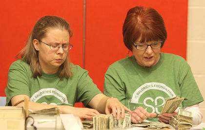 Melanie Daugherty and Elaine Helm count cash donations before the shaving of the heads begins.