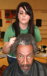 Joe Downs sits down for his fifth St. Baldrick's head shaving. His stylist is Sarah Fisher.