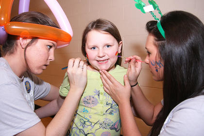 Madison Luckett, 6, gets a double rainbow from face-painters Sarah, left, and Sydney Abell.