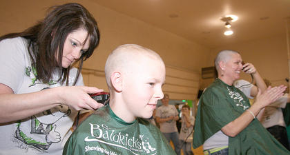Candi Skaggs cuts the hair of Matthew Miles, 10, who was the local St. Baldrick's ambassador child in 2008.